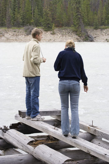 Teenage Brother And Sister Standing On Wooden Raft In Athabasca River