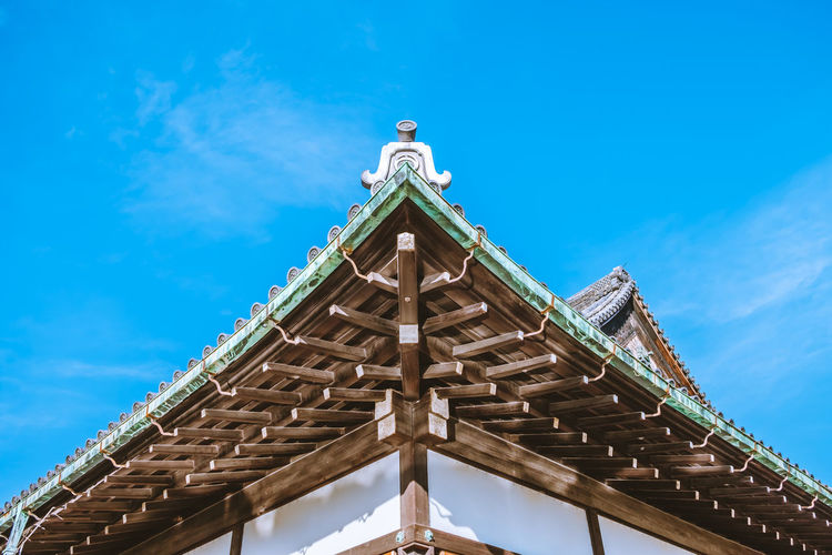 Low angle view of japanese traditional building against blue sky