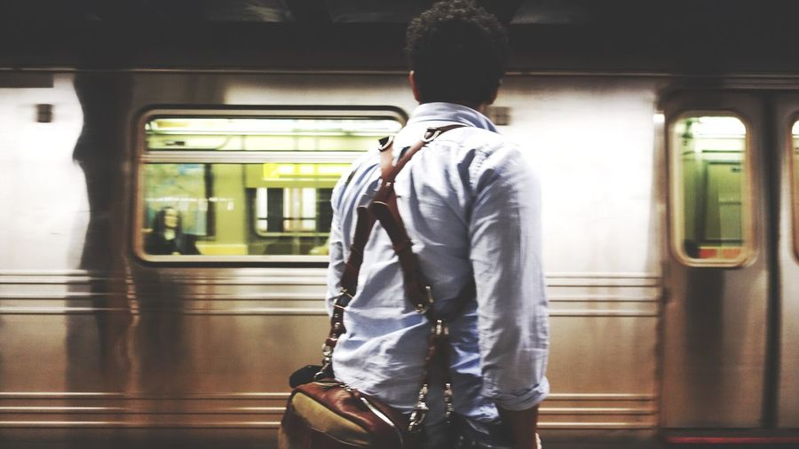 Rear View Of Man Looking At Train At Subway Station