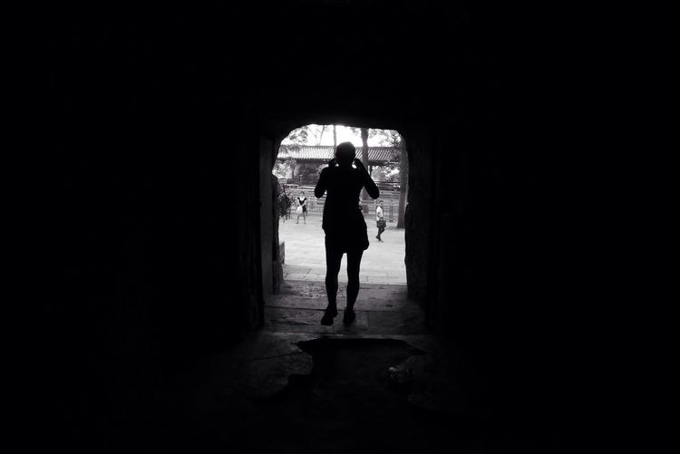 Silhouette Person Standing In Tunnel