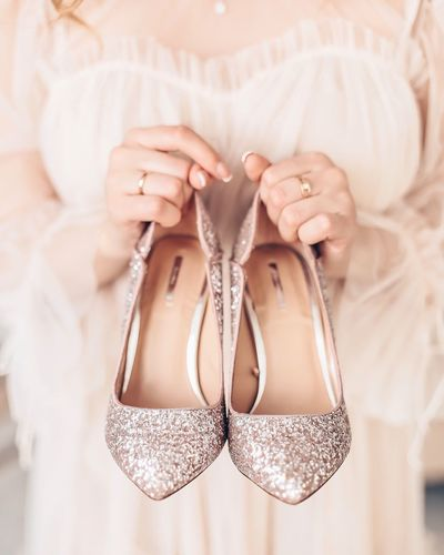 Midsection of woman holding glittering footwear