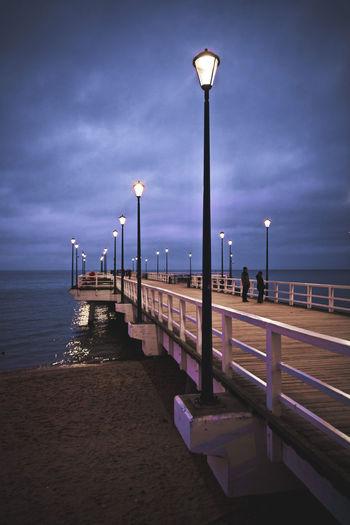 Pier on sea against sky at dusk