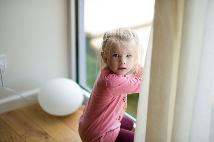 Cute girl sitting by door at home