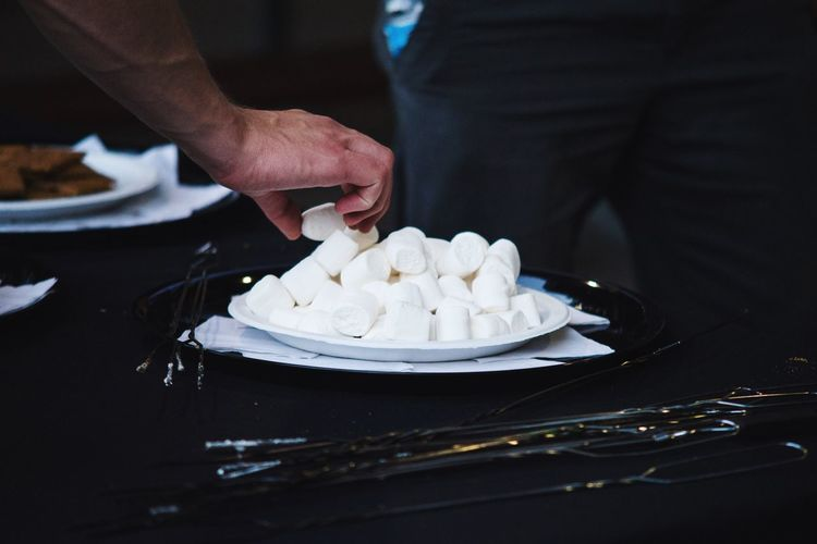 Close-Up Of Man With Marshmallows In Plate On Table