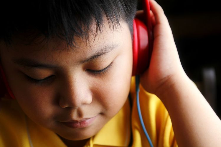 Close-up of boy listening music at home