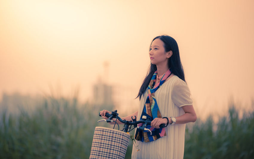 Girl Wheeling A Bike In The Field At Sunset Asian  Attractive Bicycle Bike China Chinese Countryside Eauty Female Field Girl Healthy Lifestyle Model Nature One Person People Portrait Pretty Student Sunset Vacation Wheeling Woman Young