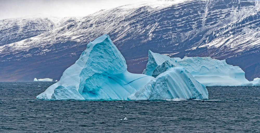 Scenic view of iceberg in sea against mountains