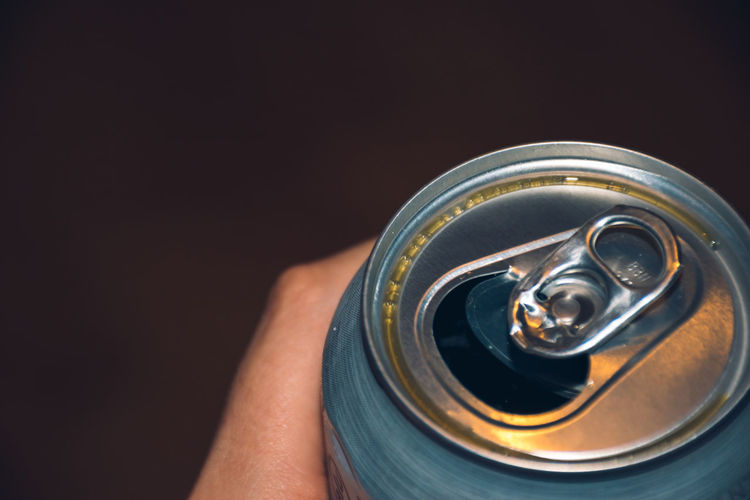 Close-up of hand holding drink against black background