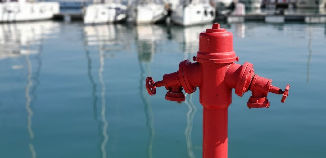 Close-up of red fire hydrant in front of harbour