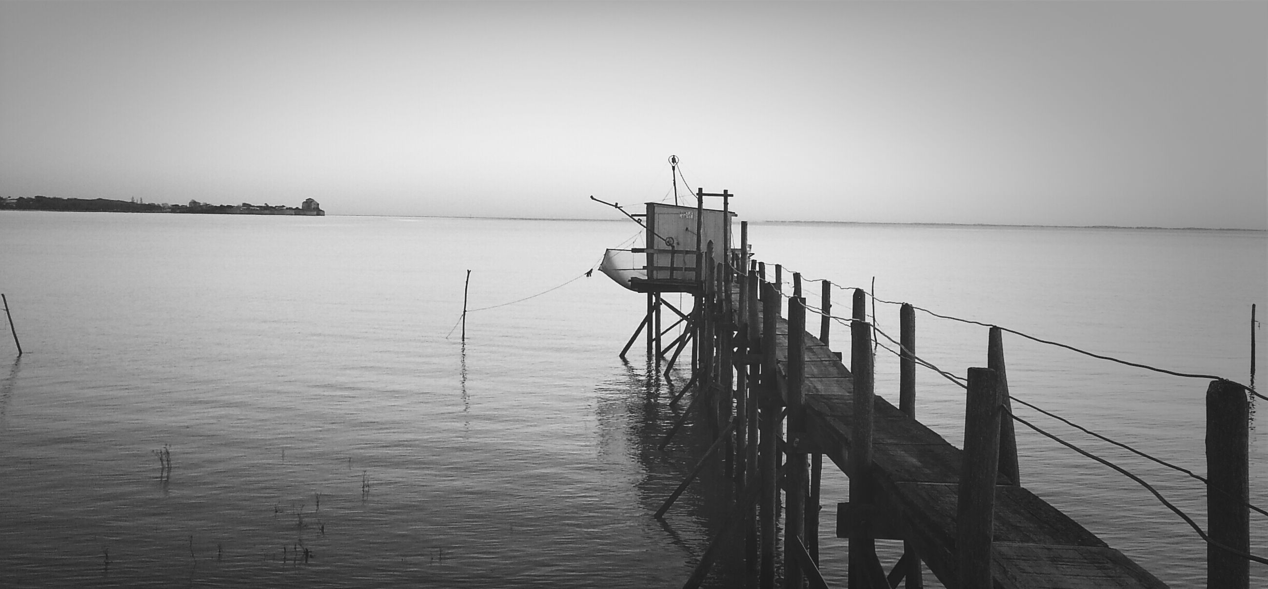 water, sea, horizon over water, tranquility, clear sky, tranquil scene, pier, copy space, nature, scenics, sky, wooden post, wood - material, beauty in nature, jetty, waterfront, built structure, day, outdoors, rippled