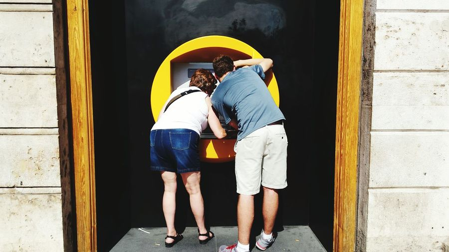 Rear view of man and woman using ATM