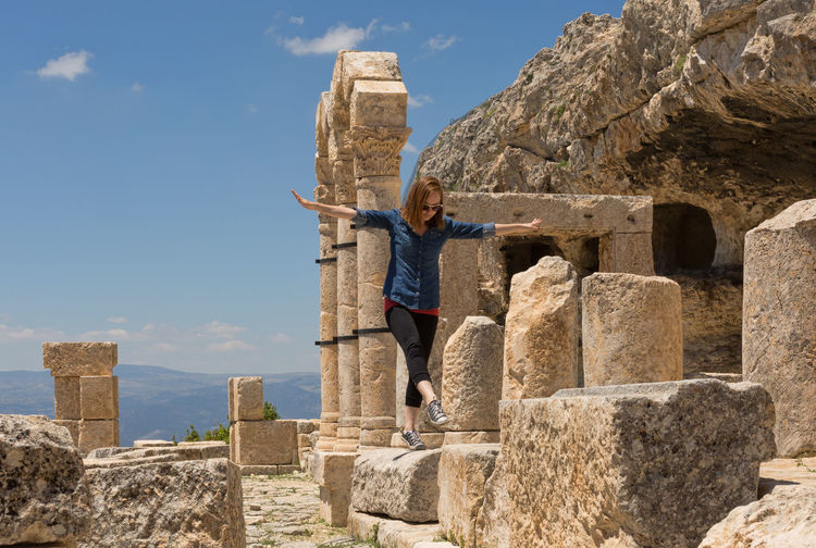 Alahan Monastery Alahan Monastery Ancient Ancient Civilization Architecture Built Structure Carvings In Stone Casual Clothing Cloud - Sky Columns And Pillars Historical Monuments Historical Sights Leisure Activity Lifestyles Monastery Mut Nature One Person Rock - Object Ruins Sky Standing Stone Material Travel Destinations Turkey Young Adult