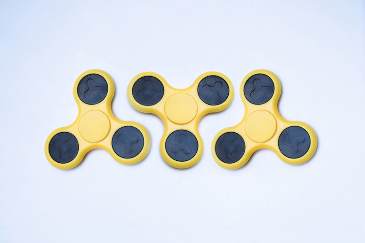 Yellow fidget spinners over white background
