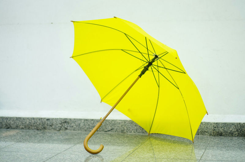 Close-up of yellow umbrella on tiled floor