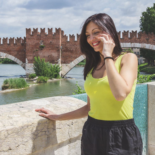 Young woman smiling while standing against built structure