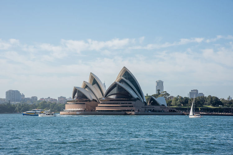 Sydney, New South Wales, Australia-December 21,2016: Landmark views of the Sydney Opera House at Bennelong Point with the Parramatta River and sailboat in Sydney, Australia Architecture Travel Destinations Water Nature Built Structure Sydney Australia Landmark International Landmark Sydney Opera House Theatre Nautical Vessel Waterfront City Building Exterior Transportation Sailboat Sailing Harbour Cruise Bennelong Point Parramatta River 20th Century Famous Place