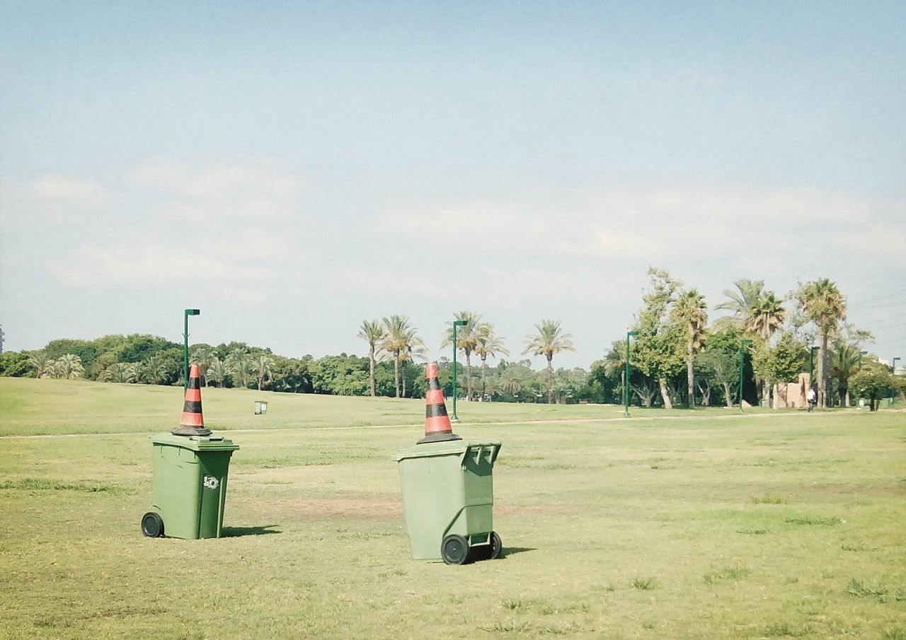 Garbage cans with traffic cones on grassy field against sky