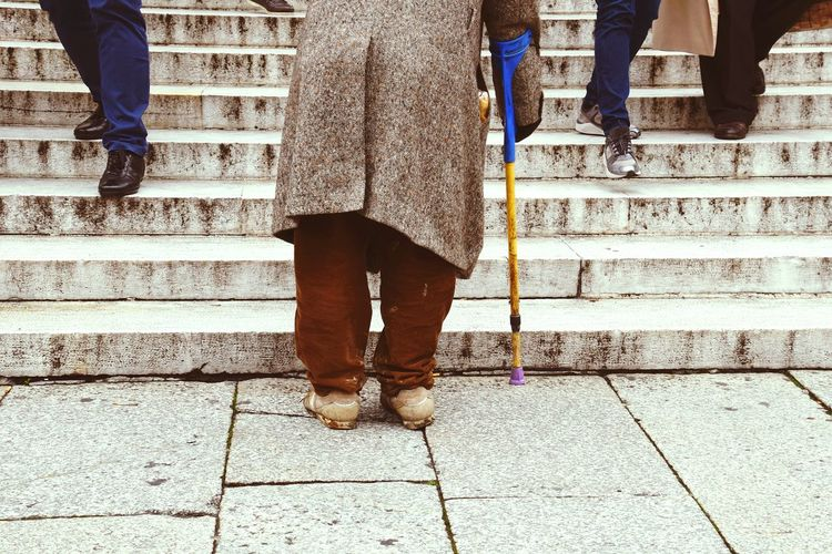 Low Section Of Person Standing With Walking Cane By Steps On Footpath