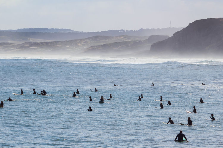 View of surfers on sea waiting for the perfect wave in baleal