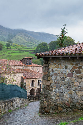 Stone wall of old building by mountain against sky