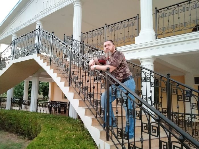 Man standing on staircase against building