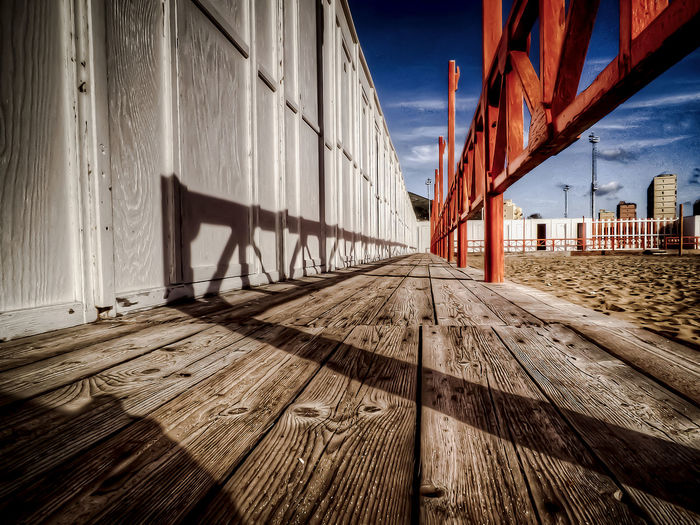 Wooden walkway by wall against sky