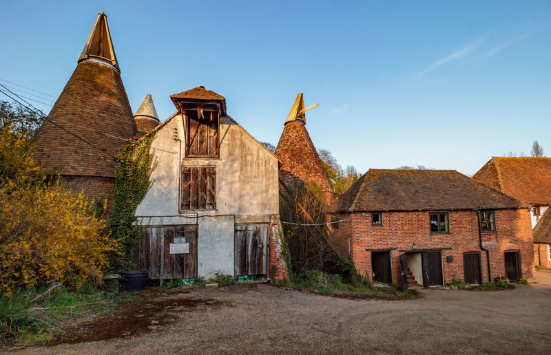 Elbridge Oast House, Kent, England. Oast House Garden Of England Travel Destinations Tourism Farm Hops Farm Yard Beer Brewing History Drying Kilm Barn Hop Pocket Celler Countryside Rural Scene Getty Images EyeEm Gallery Architecture Abondoned Built Structure Building Exterior Building Sky No People Nature Old The Past Day House Plant Clear Sky Religion Place Of Worship Outdoors Belief Tree Ancient Civilization