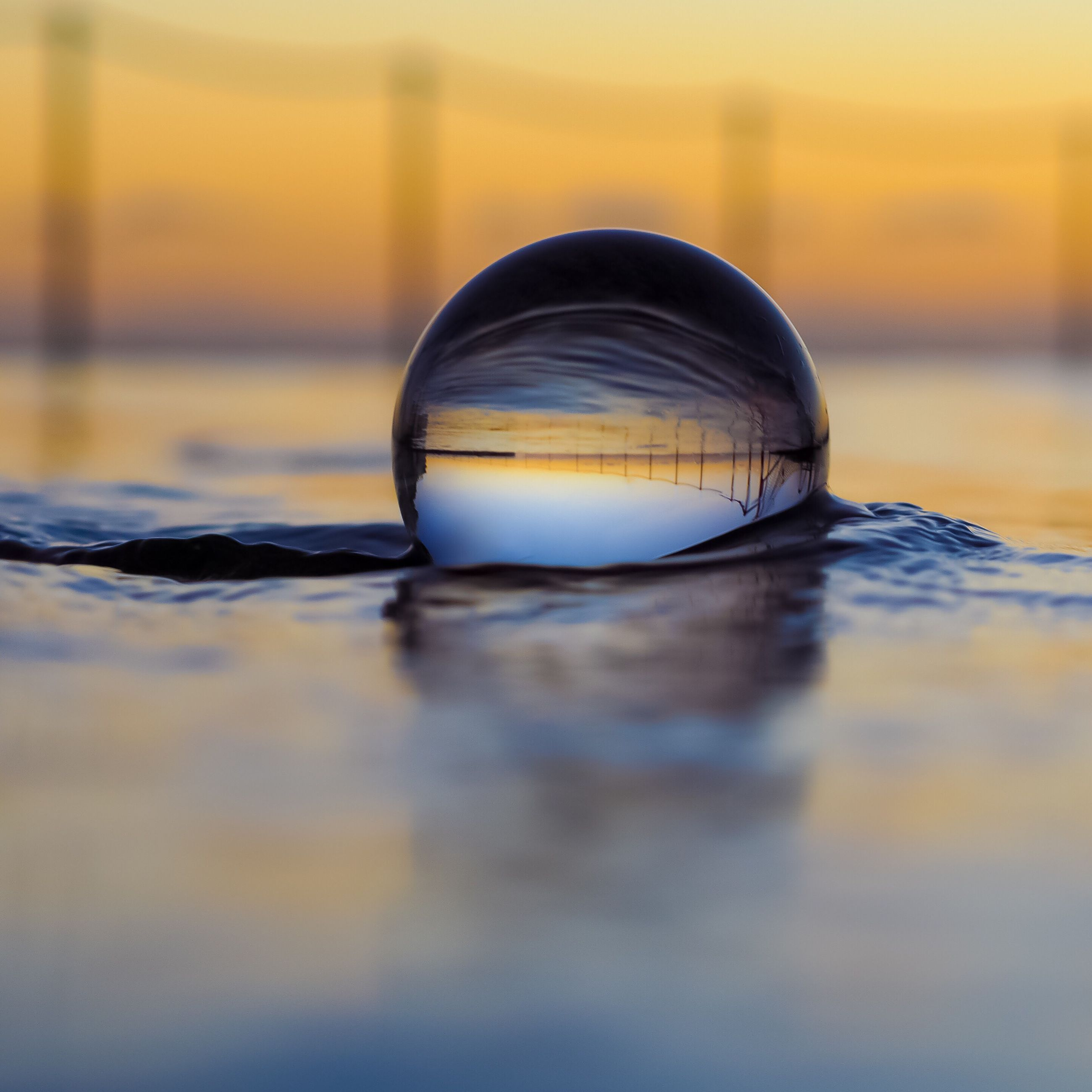 sunset, reflection, water, sphere, sky, focus on foreground, close-up, orange color, sea, beauty in nature, tranquil scene, scenics, nature, tranquility, circle, outdoors, ball, waterfront, no people, idyllic