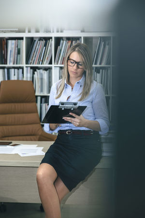 Portrait of blonde woman writing notes sitting over her desktop table. View trough of office door. Business Company Female Power Glasses Leader Smart Woman Working Writing Beauty Business Finance And Industry Businesswoman Caucasian Chief Executive  Female Headquarters Job Notebook One Person Portrait Professional Real People Sucess Vertical