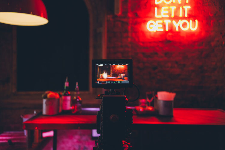 Illuminated Communication Text Western Script Lighting Equipment Technology Red Indoors  Table No People Night Close-up Electric Lamp Arts Culture And Entertainment Light - Natural Phenomenon Capital Letter Glowing Neon Sign Nightlife Red Camera Neon Lights Video Camera