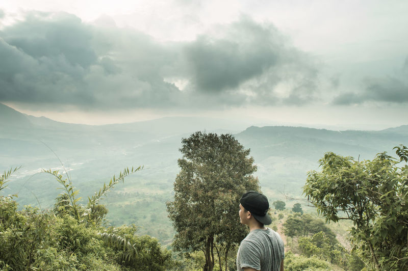 Side view of man looking at landscape while standing on mountain against cloudy sky
