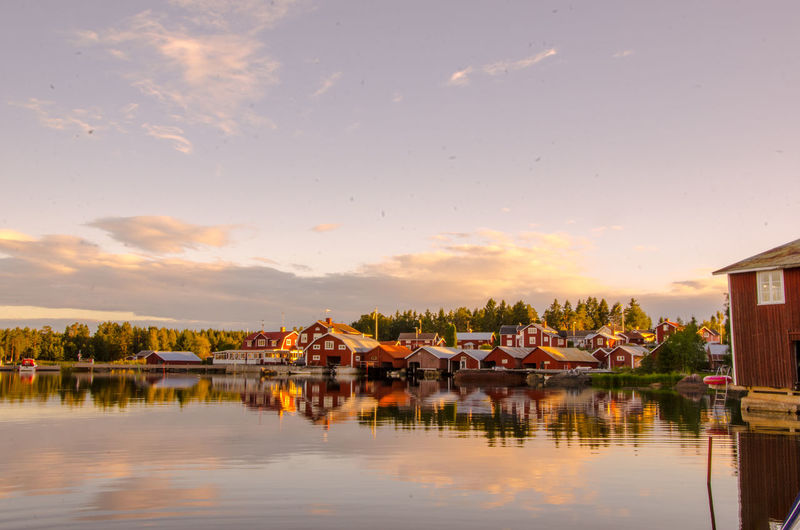 Houses by lake against sky during sunset
