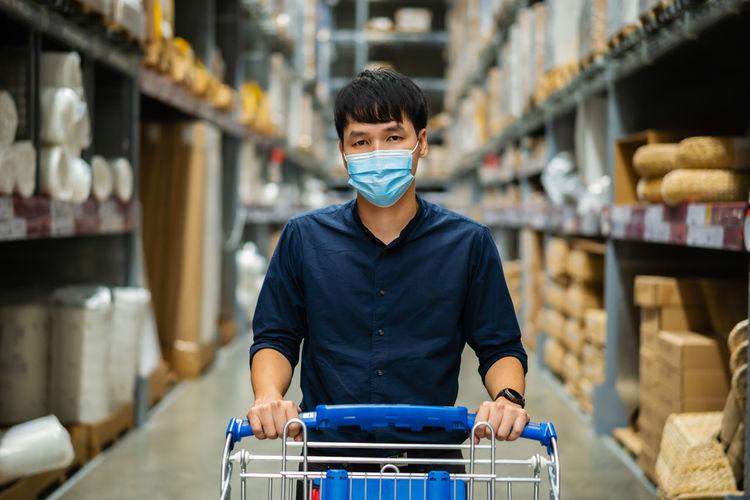 Portrait of man wearing mask working in warehouse