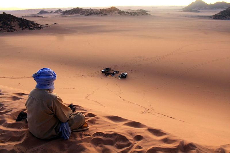 Man sitting on sand in desert