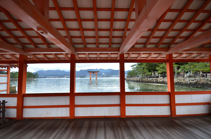 Torii Gate In Sea Seen From Itsukushima Shrine By Sea Against Sky