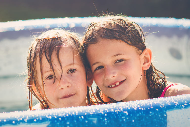 Two young girls enjoying hot summer afternoon in swimming pool Bonding Child Childhood Close-up Day Girls Happiness Headshot Leisure Activity Lifestyles Looking At Camera Love Nature Outdoors Pool Portrait Real People Sibling Smiling Summer Swimming Pool Togetherness Two People Vacations Water