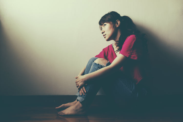 Unhappy Beautiful Woman Beauty Casual Clothing Contemplation Full Length Hairstyle Home Interior Indoors  Leisure Activity Lifestyles Looking Looking Away Melancholy Melancholy Day Mental One Person Real People Sad Side View Sitting Sorrowful Teenage Unhappy Girl Unhappy Face Wall - Building Feature Women Young Adult Young Women