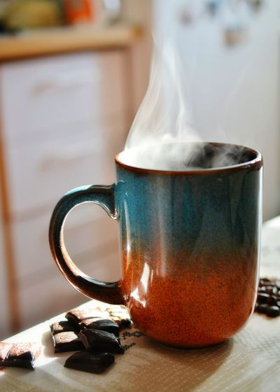 Close-Up Of Fresh Black Coffee With Chocolate On Table