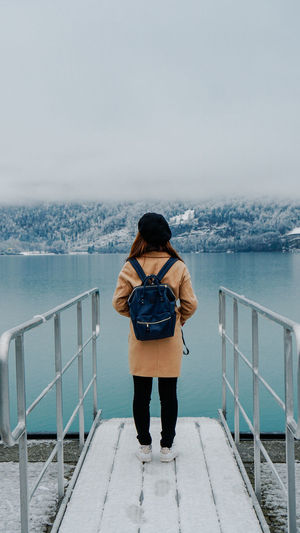 Rear view of backpack woman standing by lake during winter