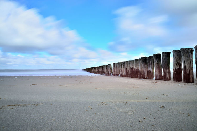 Wooden post at beach against blue sky
