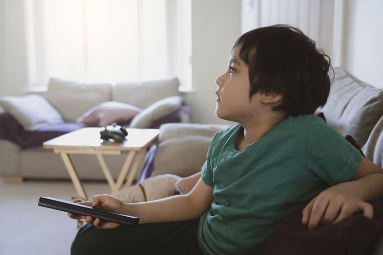 Kid lying on sofa holding remote control and watching cartoon on tv with morning light,child boy
