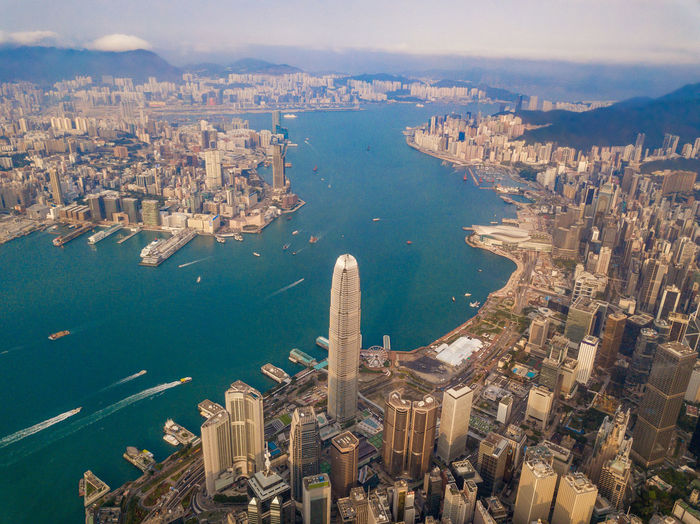 Aerial view of Hong Kong Downtown, Republic of China. Financial district and business centers in smart city in Asia. Top view of skyscraper and high-rise buildings at sunset. City Cityscape Aerial View Drone  Hong Kong HongKong Urban Downtown Above Financial District  Top Business Network Connection Landscape ASIA Buildings Skyscrapers Building Exterior Architecture Water Built Structure High Angle View Building Residential District Crowded Crowd Nature Transportation Travel Destinations Office Building Exterior River Day Skyscraper Outdoors Financial District