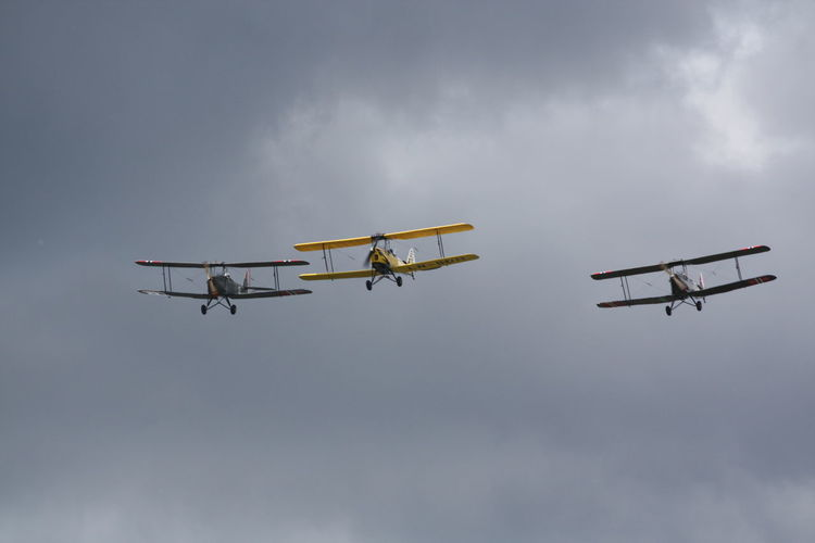 Low angle view of biplanes flying against cloudy sky