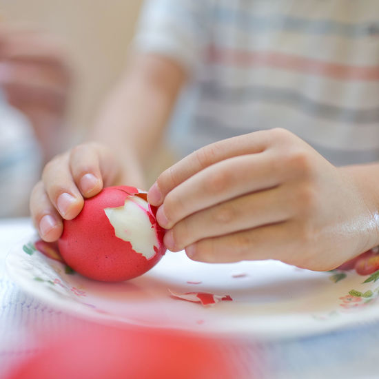 Hands of a child peeling red boiled egg