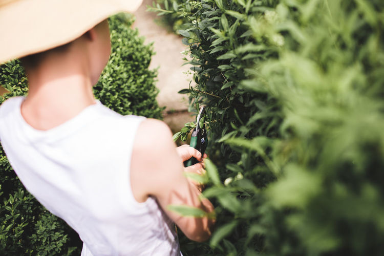 Midsection of woman standing by plant