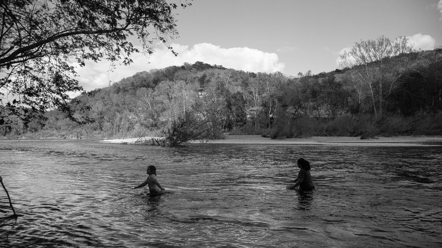 Mother And Daughter Crossing River Against Tree Mountains