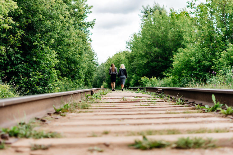 Rear view of people on railroad track amidst trees