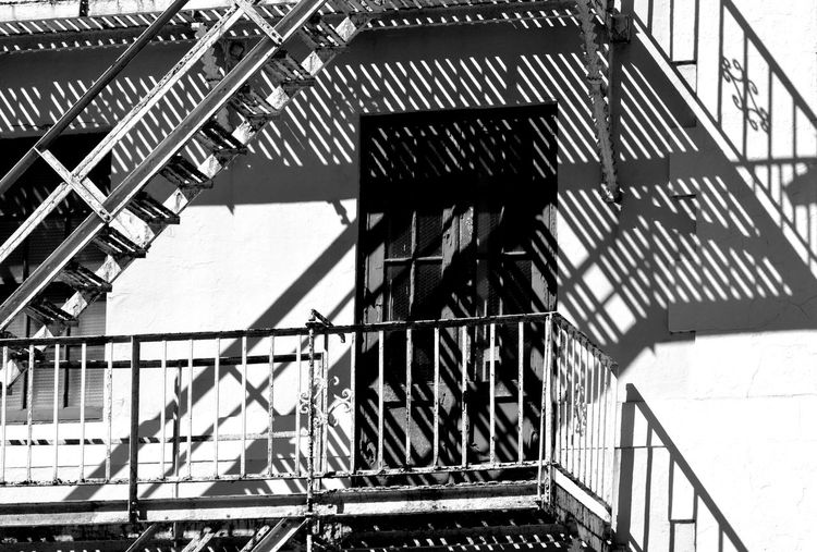 Light and shadow on building with balcony and fire escape Architecture Balcony Black And White Building Building Exterior Fireescape Light And Shadow Metal Monochrome Railing Shadow Wall Window