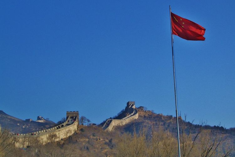 Chinese flag with great wall of china in background