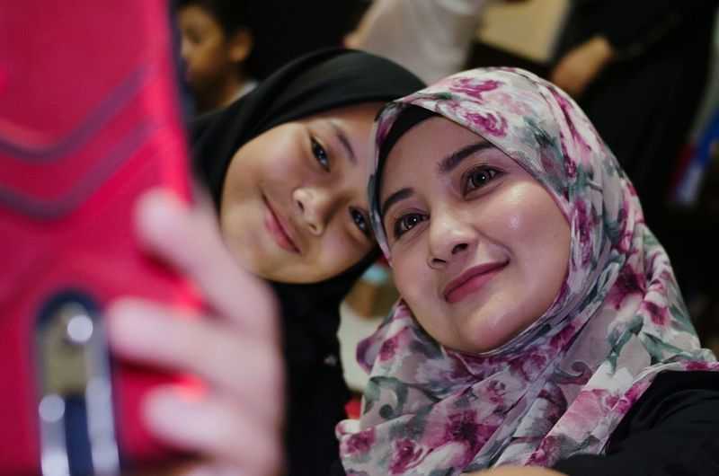 Young woman wearing hijab taking selfie with friend from mobile phone